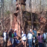 Group of people standing in a forested area, in front of an old mining installation.